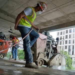 Concrete Operator cutting up concrete slab inside parking garage in downtown Austin, TX.