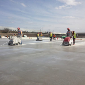 A crew of 4 early entry saw technicians cutting freshly poured concrete slab.