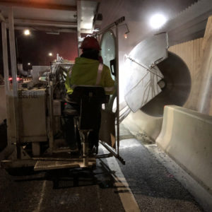 Barrier wall Machine cuts at night through a concrete Jersey Barricade