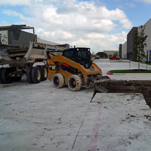 Skid steer removing panels of recently cut concrete and loading into a dump truck.