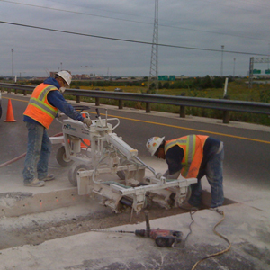 A crew (2) men dowel drilling in roadway.
