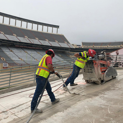 Flat saw crew of two men cutting concrete up a hill inside stadium here in Austin, Texas.